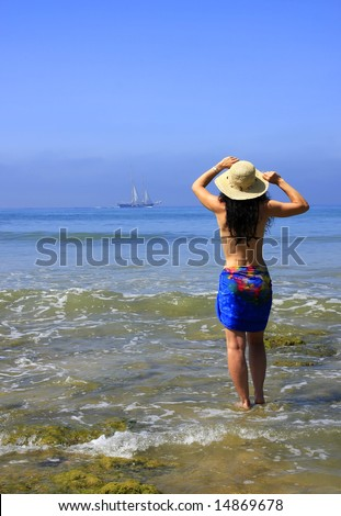 Woman standing at the beach at low tide.