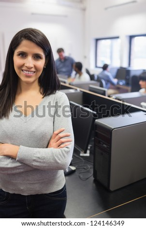 Woman standing at the front of the computer class and smiling