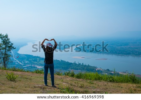 Woman standing at the peak and raising up her hand  on the mountain and river background. - stock photo
