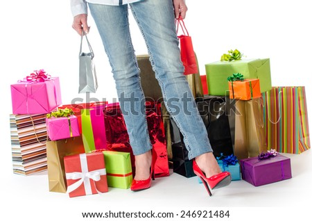 Woman standing before many gifts and shopping bags, isolated on white