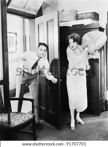 Woman standing behind a door trying to hit a man with a pillow - stock photo