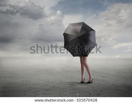 Woman standing behind an umbrella hiding her bust - stock photo