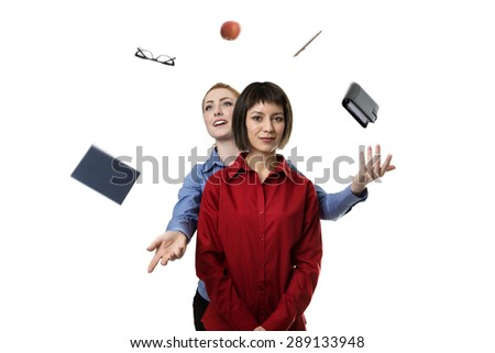 woman standing behind another woman helping her to juggle objects - stock photo