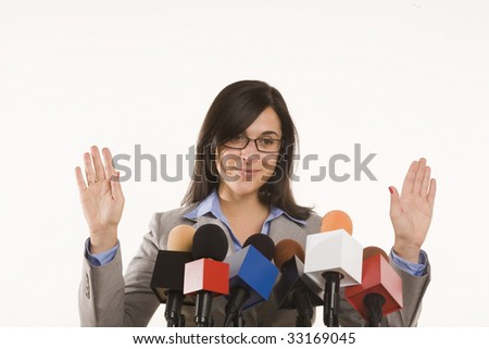 woman standing behind bank of microphones - stock photo
