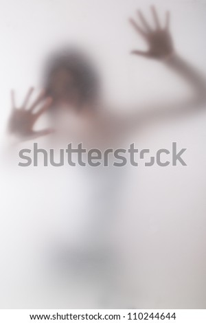 woman standing behind blurry glass/behind the window - stock photo