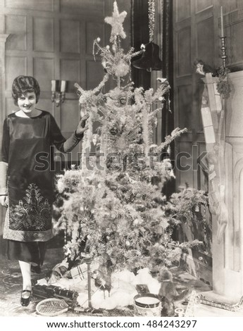 Woman standing by decorated Christmas tree