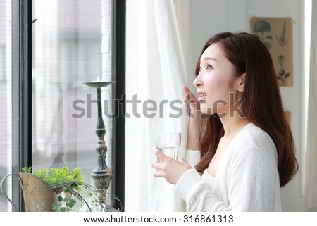 Woman standing by the window drinking water from a glass