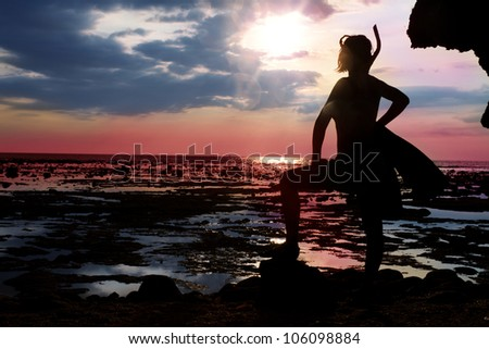 woman standing during the low tide with diving equipment  on the shore and waiting for big water in sunset - stock photo