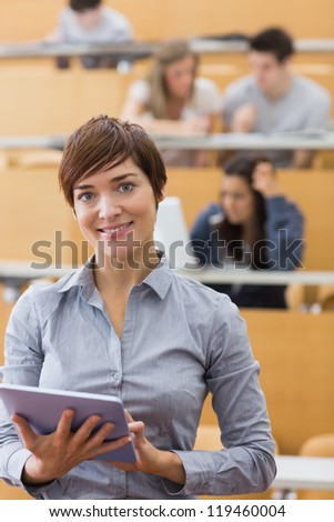 Woman standing holding a tablet computer smiling at the lecture hall - stock photo