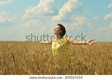 woman standing in a field hands outstretched against the sky