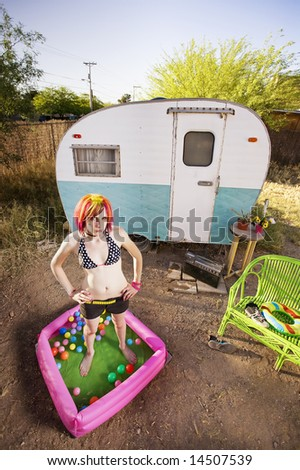 Woman standing in a play pool outside a trailer