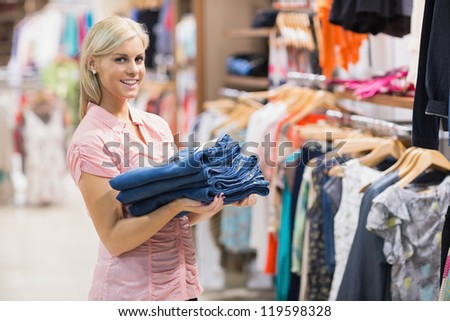 Woman standing in a shop holding jeans - stock photo