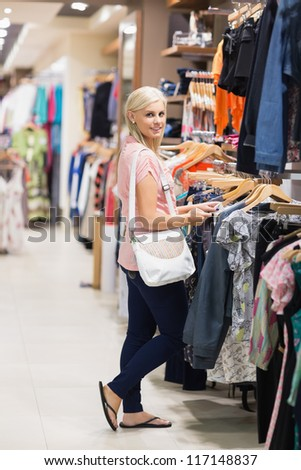 Woman standing in a shop looking at the camera smiling searching for clothes