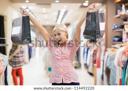 Woman standing in a shop stretching arms in the air - stock photo