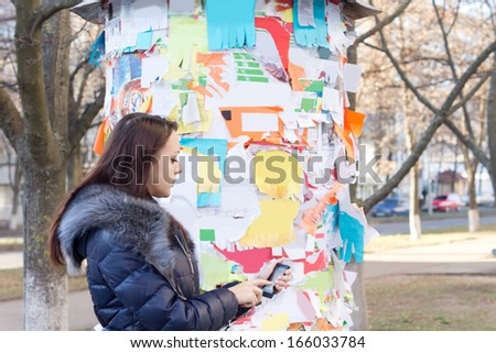 Woman standing in a town square answering an advertisement off a notice on a public noticeboard phoning the advertiser on her mobile - stock photo