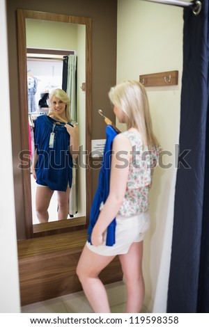 Woman standing in front of a mirror in the changing room - stock photo