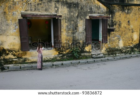 Woman standing in front of an ancient house, Hoi An Vietnam