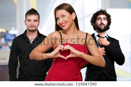 Woman Standing In Front Of Men Making A Heart Shape Sign, Indoor - stock photo