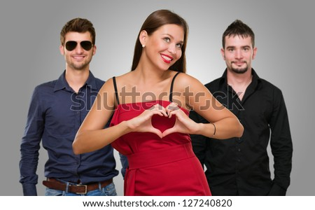 Woman Standing In Front Of Men Making A Heart Shape Sign On Gray Background - stock photo