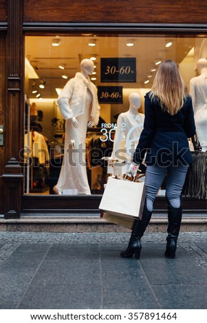 Woman standing in front of shopping window - stock photo