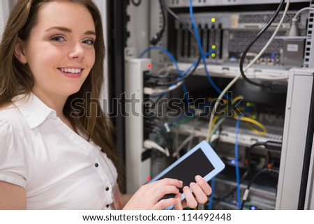 Woman standing in front of the data store while holding a tablet pc - stock photo