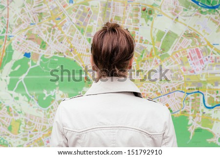 Woman standing in front of tourist city map - stock photo