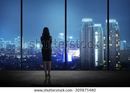 Woman standing in his office looking at the city at night. Business success concept - stock photo