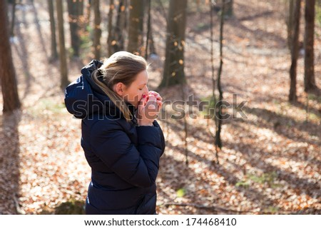 Woman standing in the forest during wintertime with a thick jacket
