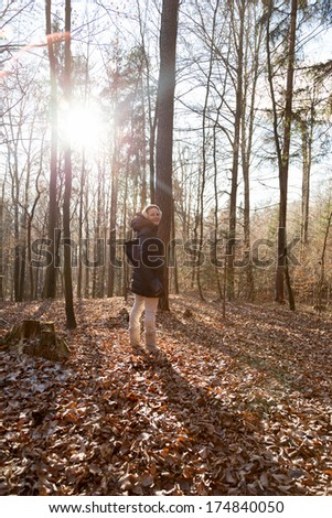 Woman standing in the forest during wintertime with a thick jacket - stock photo