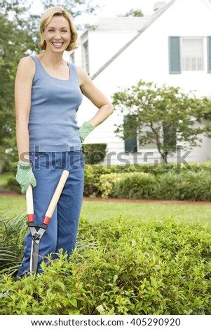 woman standing in the garden holding shears