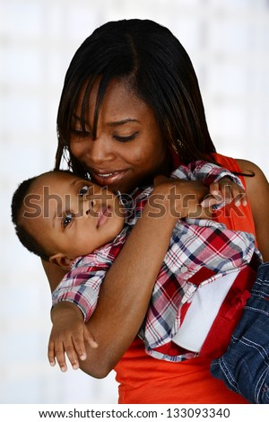 Woman standing in the living room of her home with a baby - stock photo