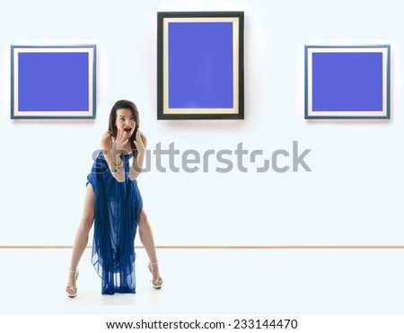 Woman standing inside a gallery in front of three picture frames and screaming. Images are fill with blue color useful for copy space. NOTE:This image is composite of more photos. - stock photo