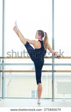 Woman standing near barre in fitness center - stock photo