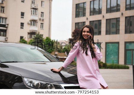 woman standing near car and calling by phone