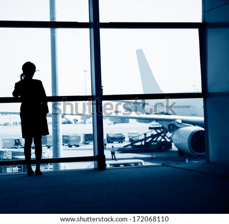 woman standing near the airport window, waiting for flight departure. - stock photo