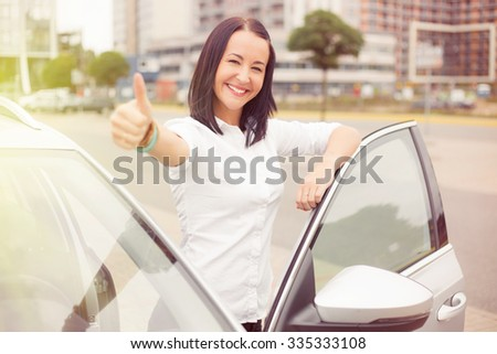 Woman standing next to car with thumbs up  - stock photo