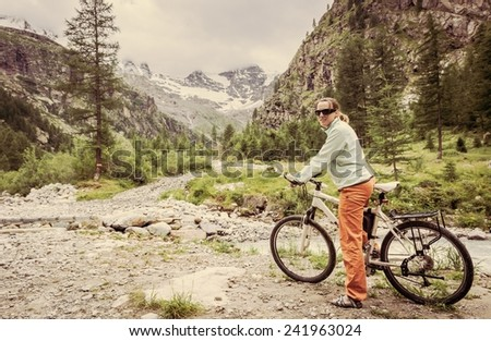 Woman standing on a bike in front of a river - stock photo