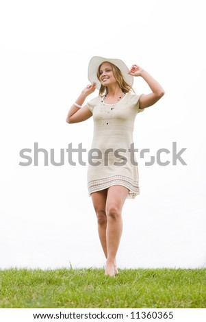 Woman standing on a grassy hill and holding her hat