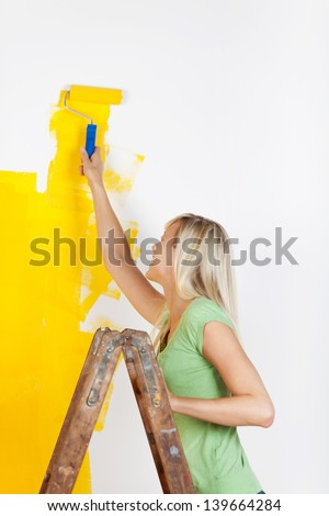 Woman standing on a ladder painting a white wall with a vibrant yellow paint using a roller as she redecorates her house