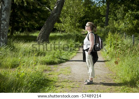 Woman standing on a path enjoying the forest in evening light - stock photo