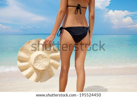 Woman standing on a perfect beach holdin a sun hat - stock photo