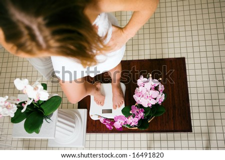 Woman standing on a scale in a spa setting - stock photo