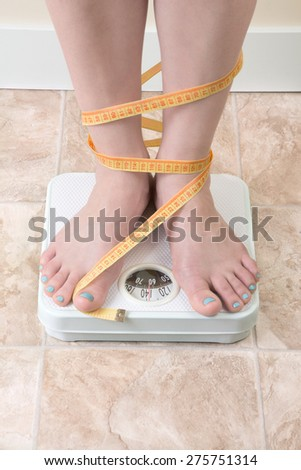 Woman standing on a weight scale