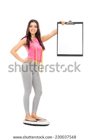 Woman standing on a weight scale and holding a clipboard isolated on white background - stock photo