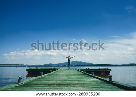 Woman standing on a wooden jetty enjoying the sunshine with arms up. Woman on a pier on the lake greeting the sun with arms wide open.   - stock photo