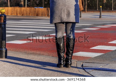 Woman standing on crossroad and waiting to cross - stock photo