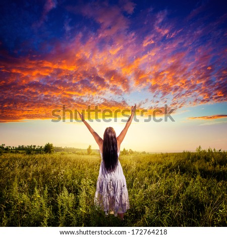 woman standing on field over sunset under beautiful skies, freedom concept - stock photo