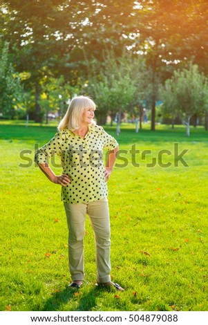 Woman standing on grass. Elderly female smiling. Admiring the views of nature. Most picturesque place for photos.