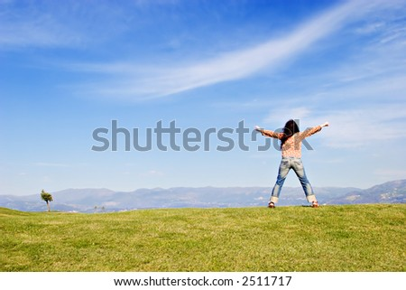 Woman standing on grass field, with arms wide open.