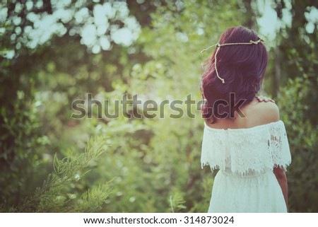 woman standing on green bokeh background. Woman in meadow. travel and sunset in vintage style  - stock photo